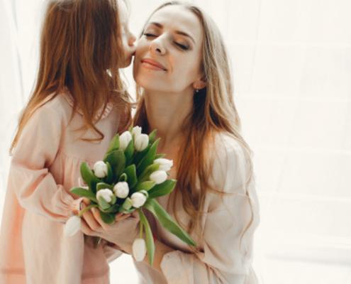 Dia mundial da gentileza: menina presenteando a mãe com flores.